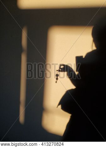 Defocus Shadows Of Woman Hand Holding Bunch Of Keys In Fingers. Female Silhouette Of Shadow On Wall