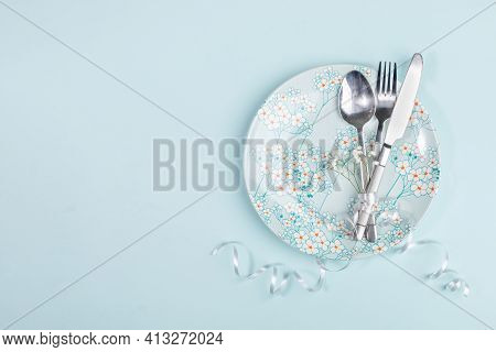 Top View Easter Table Setting With Flatware On Light Blue Plate With Spring Flowers Decor On Pastel