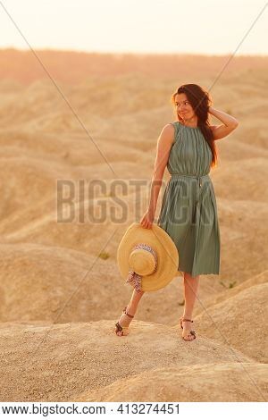 Young Beautiful Lonely Woman With Long Hair In Blue Long Summer Dress With Straw Hat In Hand Standin