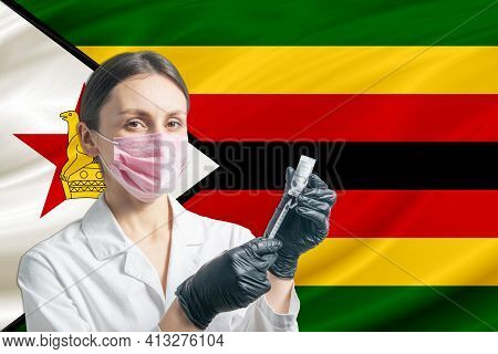 Girl Doctor Prepares Vaccination Against The Background Of The Zimbabwe Flag. Vaccination Concept Zi