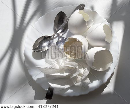 Shells Of Boiled Eggs With The Remains Of Yolk And Boiled Egg White, Used Paper Napkin, Teaspoons, A
