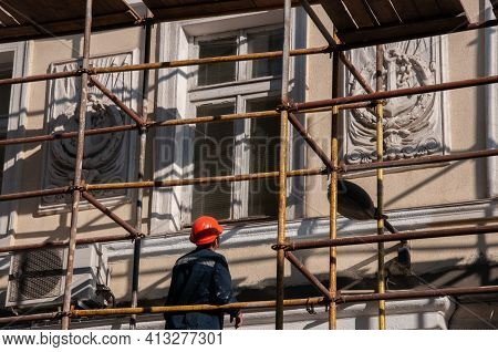 Man Builder In Orange Construction Helmet Working From Scaffolding To Renovate Building Wall With Or