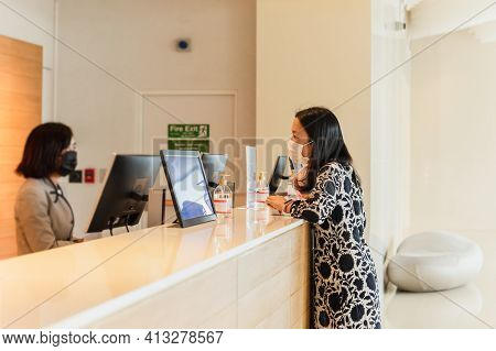 Woman Hotel Guest And Receptionist At Hotel Counter Wearing Medical Mask Against Virus
