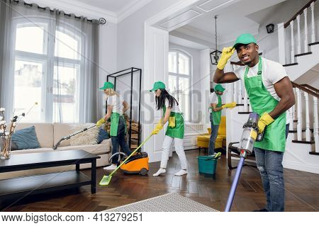 Mixed Race Janitors Doing Spring Cleaning Of House