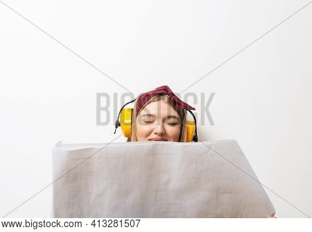 Happy Girl In Protective Headphones Sitting On Floor With Paper Blueprint. Home Remodeling After Mov