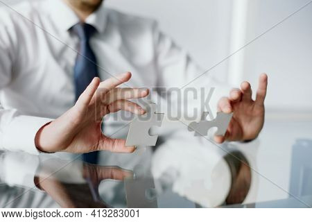 Image Of Businessman Connecting Elements Of White Puzzle.