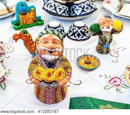Samara, Russia - October 5, 2019: Uzbek Ceramic Souvenirs On The Table. Smiling Central Asian Man Wi