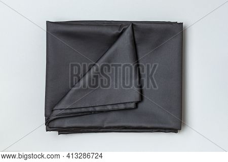 Close-up Top View Of A Set Of Dark Bed Sheets And Duvet Cover On A Gray Background.