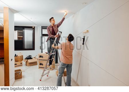 Young Man On A Stairway Changing A Light Bulb While His Friend Helps To Hold The Ladder. Gay Couple