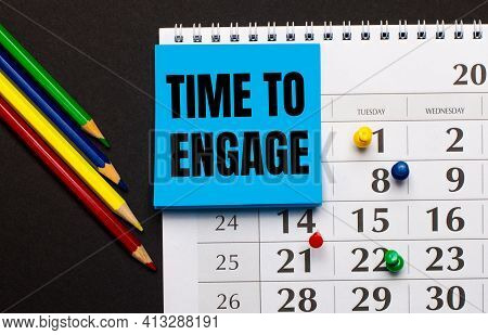 The Calendar Has Light Blue Note Paper With The Text Time To Engage. Nearby Colored Pencils On A Dar