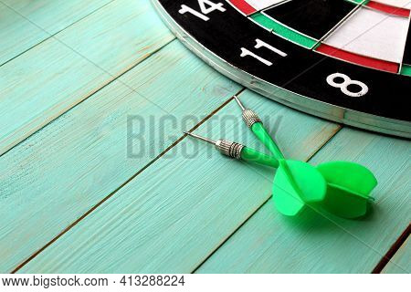 Dart Board With Two Darts Lies On A Wooden Background