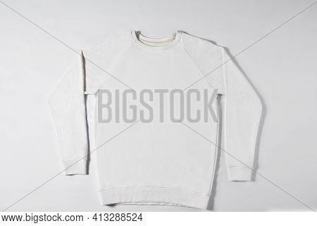White Raglan Lying On A Light Background. In A Studio. Jacket Without Inscriptions And Logos On The