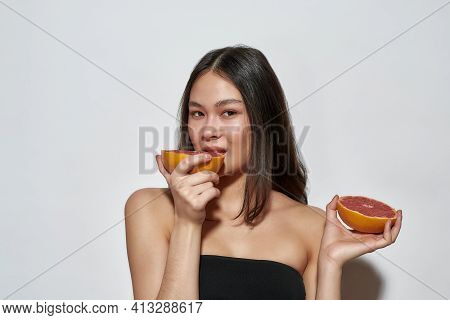 Young Girl With Grapefruit In Hand Posing On White Background. Asian Model With Grapefruit In A Ligh