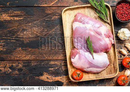 Raw Fillet Of Farm Turkey Thigh. Dark Wooden Background. Top View. Copy Space