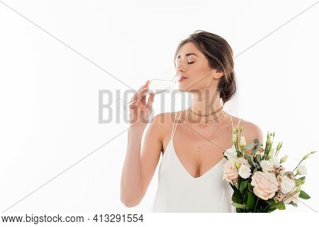 Young Fiancee Holding Wedding Bouquet While Drinking Champagne Isolated On White.
