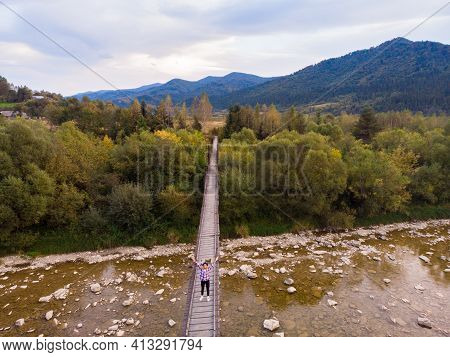 Beautiful Woman In Hat And Dress Walk On Wooden Bridge Across Mountain River. Aerial Top View, Trave
