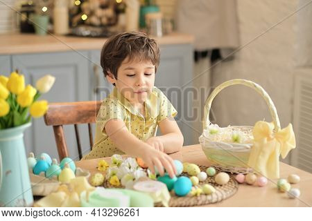 Little Boy Puts Colored Eggs In A Wicker Easter Basket. Easter Preparation Concept