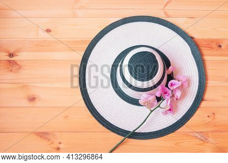 White Summer Hat  And Purple Orchid On Wooden Background. Summer And Tropical Holidays Concept. Top