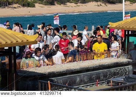 China, Hainan Island, Sanya - January 21, 2020: Believers Praying And Offering Incense Sticks For Bo