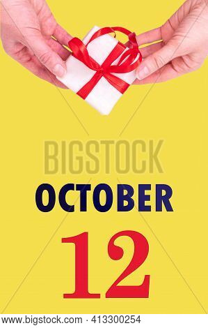 October 12th. Festive Vertical Calendar With Hands Holding White Gift Box With Red Ribbon And Calend