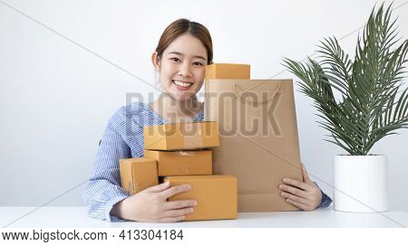 Young woman embraced a mailbox and a brown paper bag in preparation for the delivery of her order, N