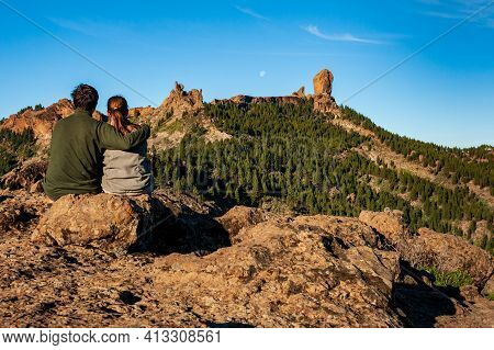 Young Couple From Behind Sitting And Watching Roque Nublo, Symbolic Natural Monument Of Gran Canaria