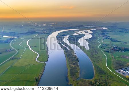 Aerial View Of Huge Lowland River Ijssel Through Sunset Landscape. Zwolle, Overijssel Province, The