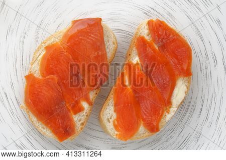 Two loaves of bread with smoked red salmon on white plate