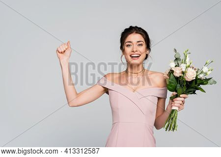 Excited Fiancee Showing Win Gesture While Holding Wedding Bouquet Isolated On Grey.