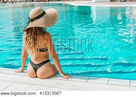 Resort Wellness. Young Sexy Woman In Straw Hat, Bikini Swimsuit, Sunglasses In Blue Pool Water. Stra