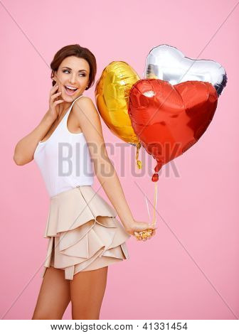 Vivacious woman with colourful shiny red, gold and silver heart shaped party balloons on a pink background