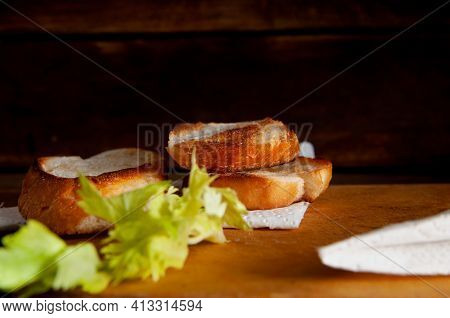 Toasted White Bread With Herbs On A Table Background.