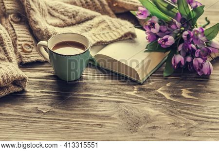 Spring Morning Coffee. A Cup Of Coffee On A Wooden Table, An Open Book And A Warm Sweater Against Th