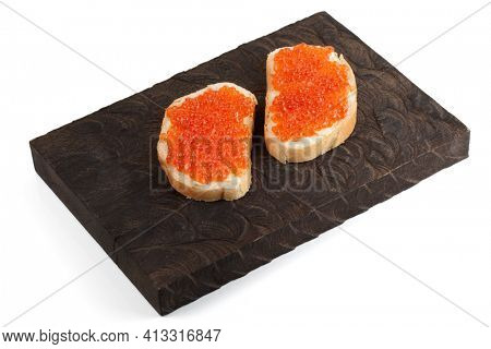 Open-face sandwiches with salmon roe on wooden board, isolated on white background