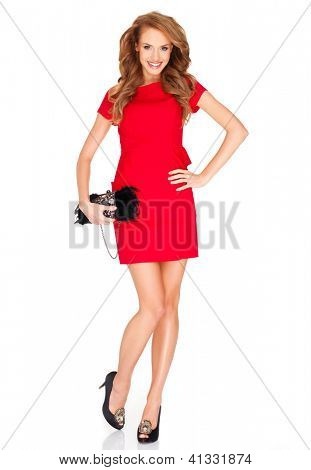 Beautiful trendy fashion blonde model in a stylish red miniskirt smiling happily as she poses with a modern handbag on a white studio background