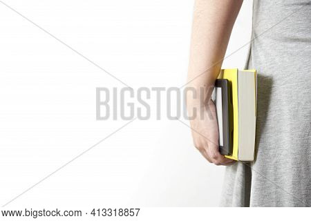 Yellow Book And Electronic Reader Held By An Unrecognizable Young Woman In A Gray Dress. Image With