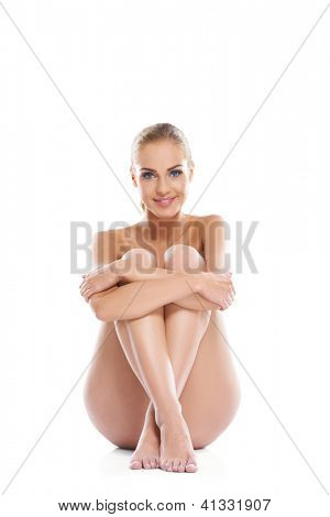 Artistic portrait of a beautiful woman posing implied nude sitting on the floor with her legs drawn up in front of her, studio portrait on white