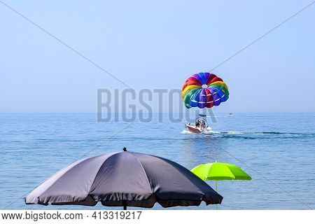 Multi-colored Parachute With Man On The Background Of The Sea, Blue Sky And Open Beach Umbrellas. Th