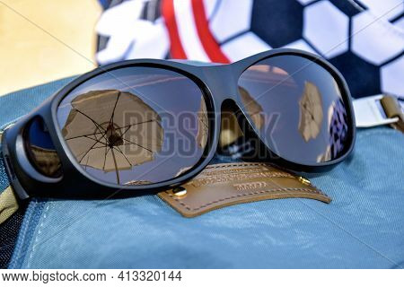 Summer Vacation, Beach Holiday. Reflection Of White Beach Umbrellas In Sunglasses. Sunglasses On Bac