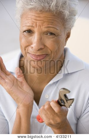 Woman Holding Wrench Looking Unsure