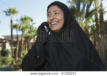 Happy Indian woman in burka communicating on mobile phone