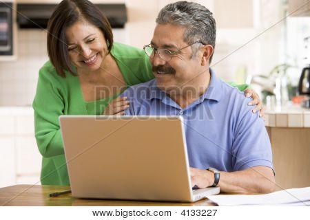 Paare in Küche mit Laptop lächelnd