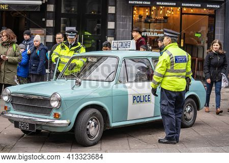 Policemans Standing By His Police Car.police Sign On An Austin Patrol Car.austin1300 Police Panda Ca