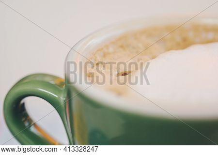 Coffee In Green Cappuccino Ceramic Cup With Frothy Foam, Latte Capuccino Mug Closeup. Hot Coffee Lat