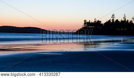 A Beach Sunset With Water Reflection Near Tofino British Columbia Canada During Spring Break.