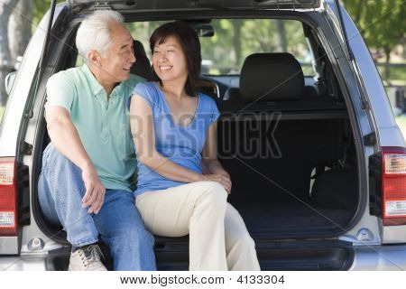 Couples Sitting In Back Of Van Smiling