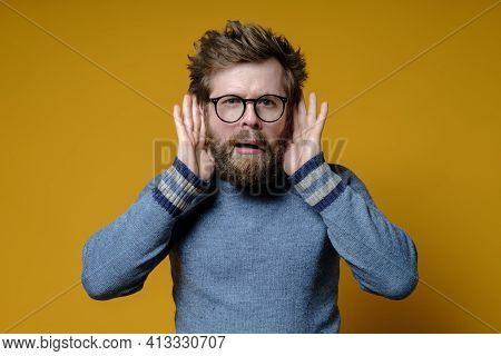 Strange Hairy Man Tries Something Overheard Having Put Hands To Ears And With A Bizarre Expression O