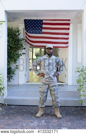 African american male soldier standing in front of american flag outside home. soldier returning home to family.