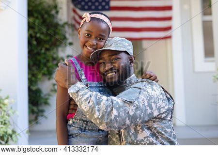 Portrait of african american soldier father hugging smiling daughter in front of house. soldier returning home.