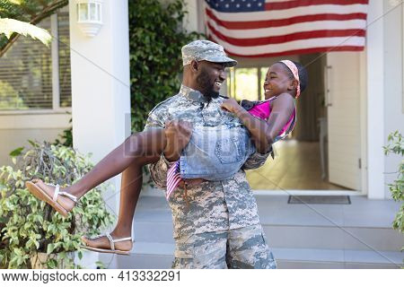 African american soldier father carrying smiling daughter in front of house. soldier returning home to family.